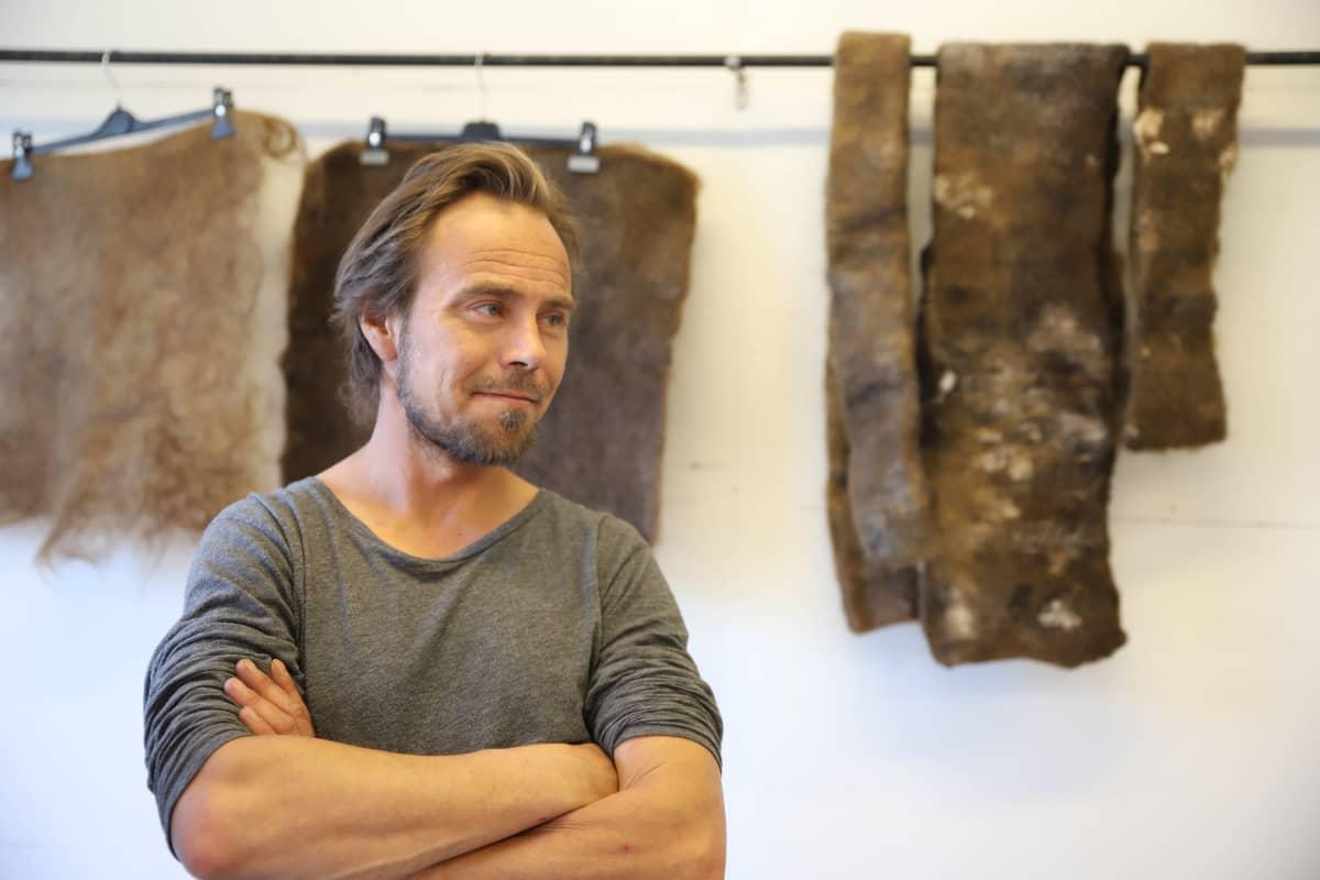 Mies seisoo seinällä roikkuvien hiuskuidusta tehtyjen mattojen edessä