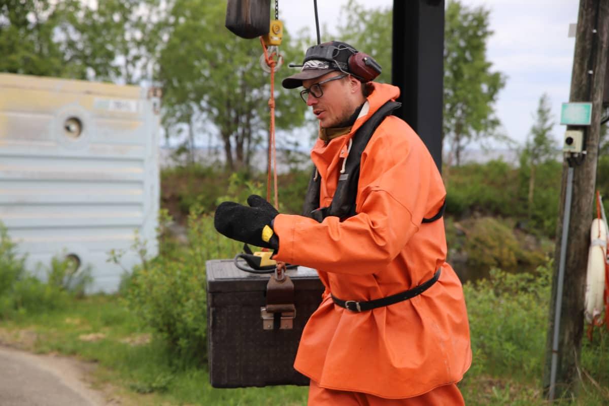 kalastaja Tom Johansson kuljettaa kalalaatikkoa vinssin avulla