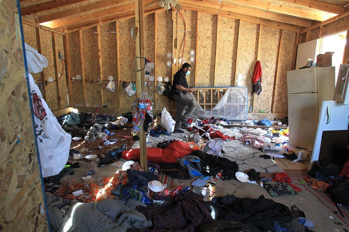 Poliisi tutkii rähjäistä huonetta, jossa pidettiin kidnapattuja siirtolaisia.