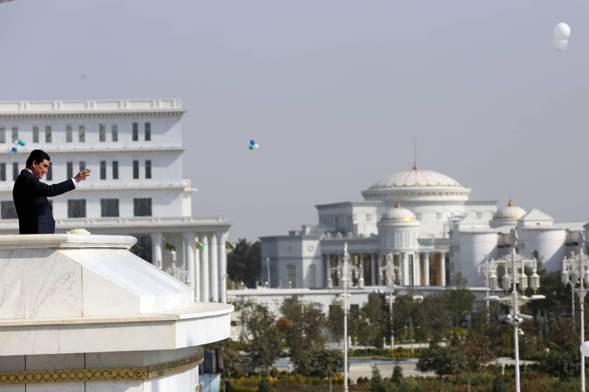 Turkmenistanin presidentti seisoo palatsin parvekkeella mustassa puvussa ja vilkuttaa alaspäin. Taustalla näkyy suuria valkoisia palatsimaisia rakennuksia.
