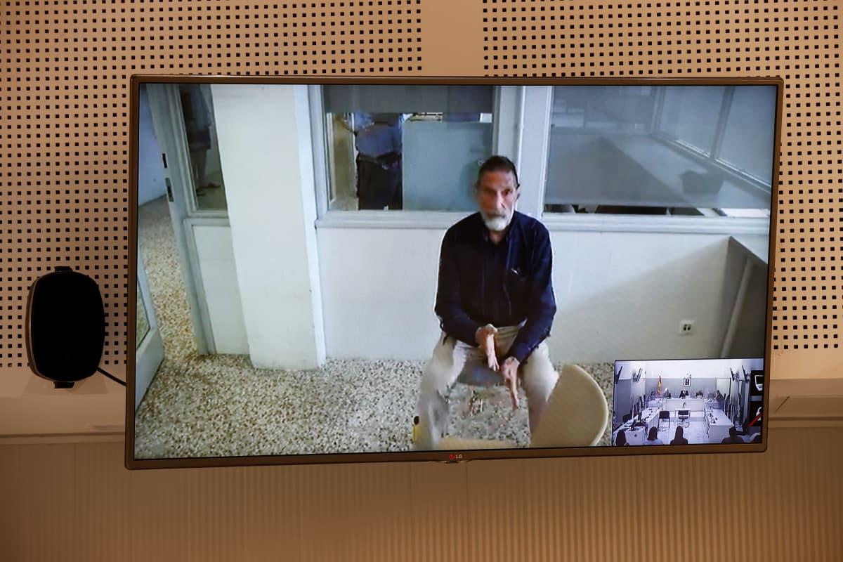 John Mcafee istuu tuolilla televisiokuvasas. Hänet kuvattiin videokuulemisessaan kesäkuun 15. päivä.