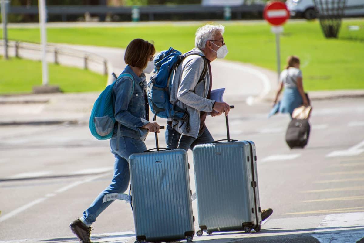Maskipäinen pariskunta kuljettaa matkalaukkuja Mallorcan lentokentällä