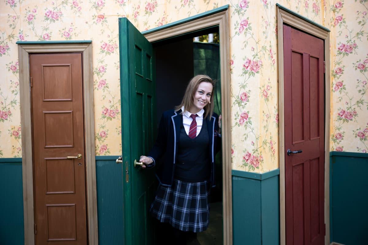Kuvassa on seinä, jossa on kukkatapettia ja kolme ovea. Nainen kurkkaa keskimmäisestä ovesta. Naisella on yllään koulupuku.