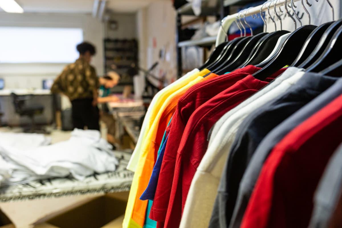 Vaaterekki täynnä erisiä vaatteita. Taustalla sumeana Hamid Arifai ja Omar Arifai työpisteellään.