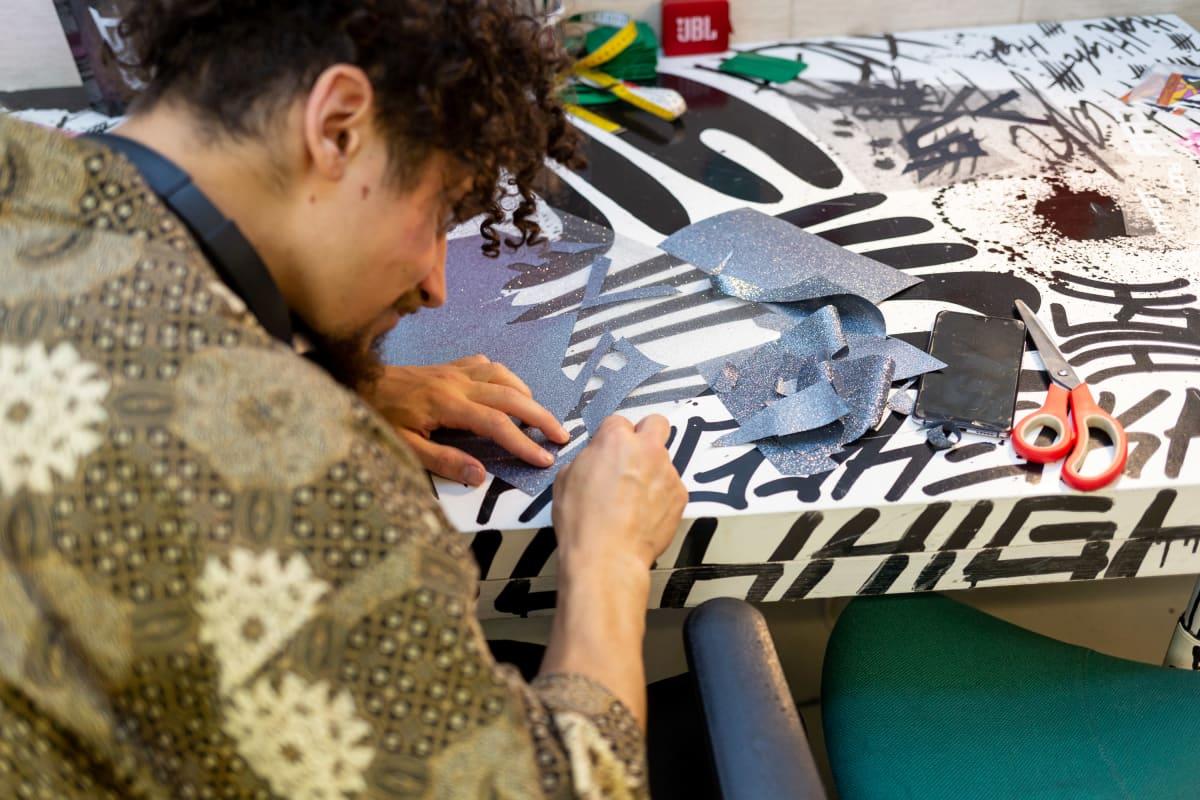 Hamid Arifai nyppimästä vaatteen printtaamiseen tarkoitetusta muovista ylijäämä muovia.