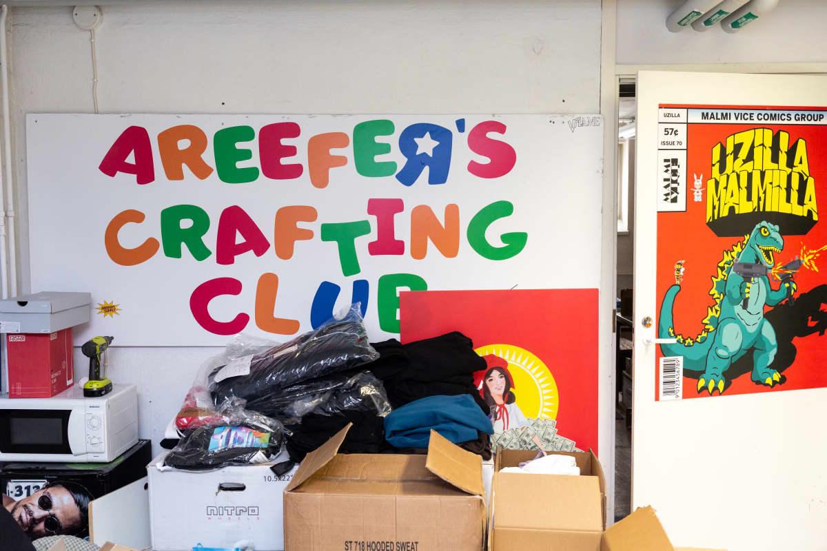 """Pahvilaatikoita ja pusseja joissa vaatteita. Laatikoiden takana seinällä taulu jossa lukee """"arefeers crafting club"""" ja juliste jossa lukaa """"uzilla malmilla"""""""