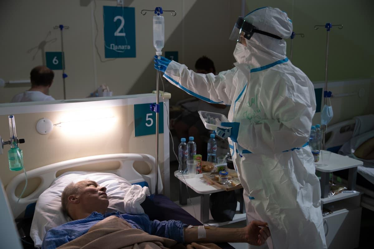 Terveydenhuollon työntekijä tarkisti potilaan vointia Moskovan Krilatskojen jääpalatsiin rakennetussa koronasairaalassa.