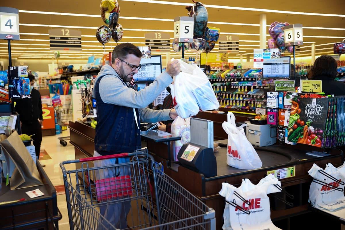 Mies on ostoksineen kaupan tiskillä ilman kasvomaskia.