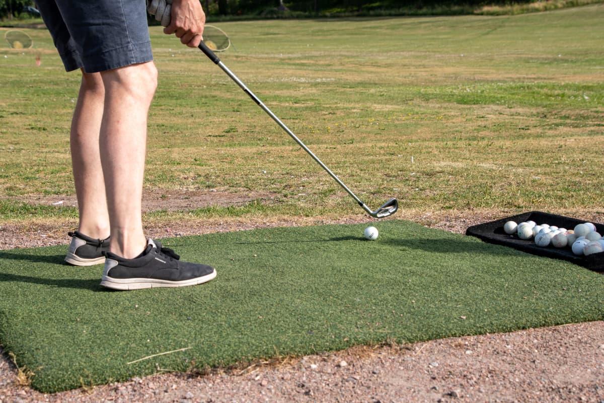 Någon håller på att slå en golfboll med golfklubba. I bilden syns tvp ben, golfboll, golfklubba och golfbanan i bnakgrunden.
