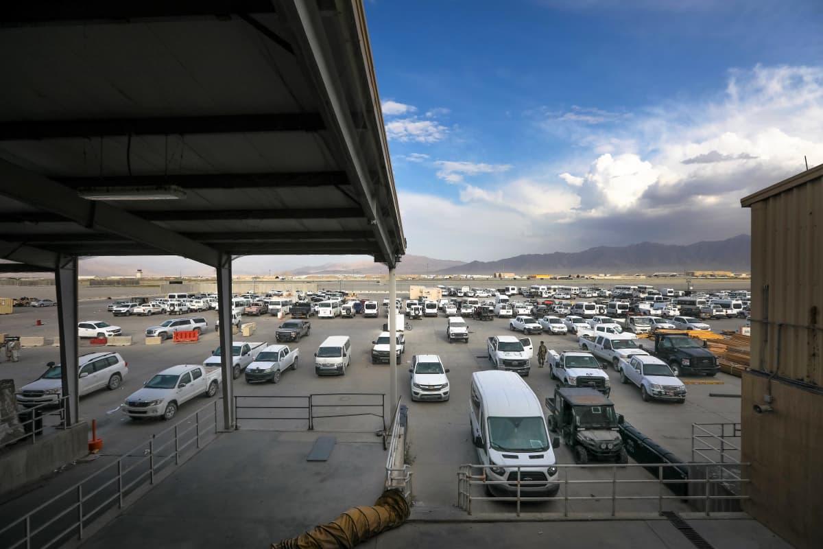 Parkkipaikalla on kymmeniä autoja. Taustalla näkyy vuoristoa, joiden yllä roikkuu suuria pilviä.