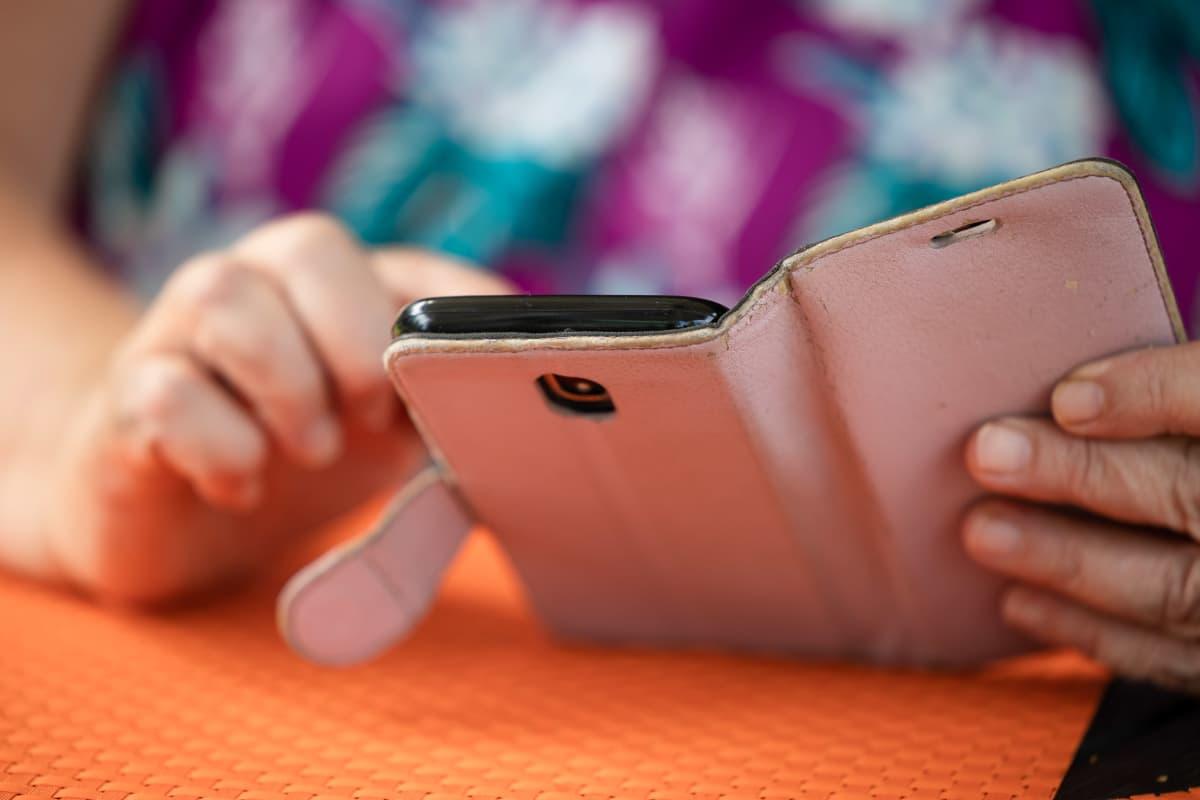 Päivi Kortelainen selaa puhelimella lähettämiään sähköposteja Eksotelle.