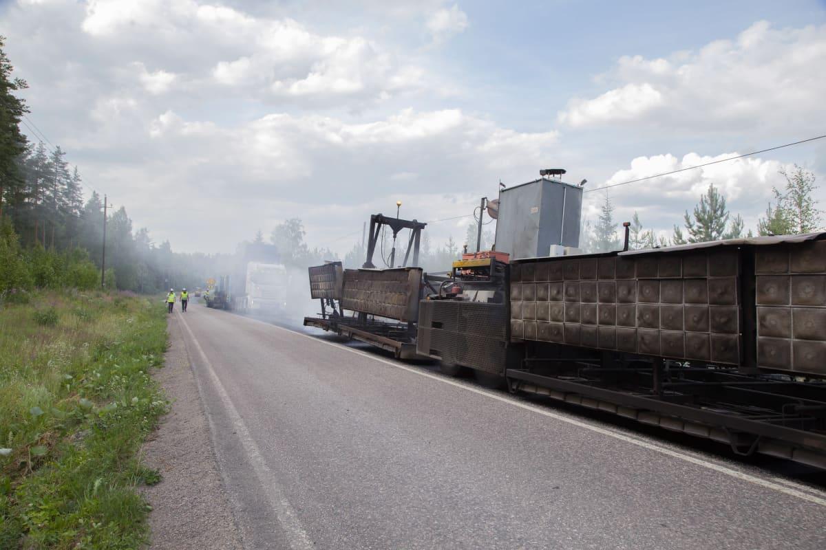 Asfalttikoneita ja työntekijöitä asfalttityömaalla.