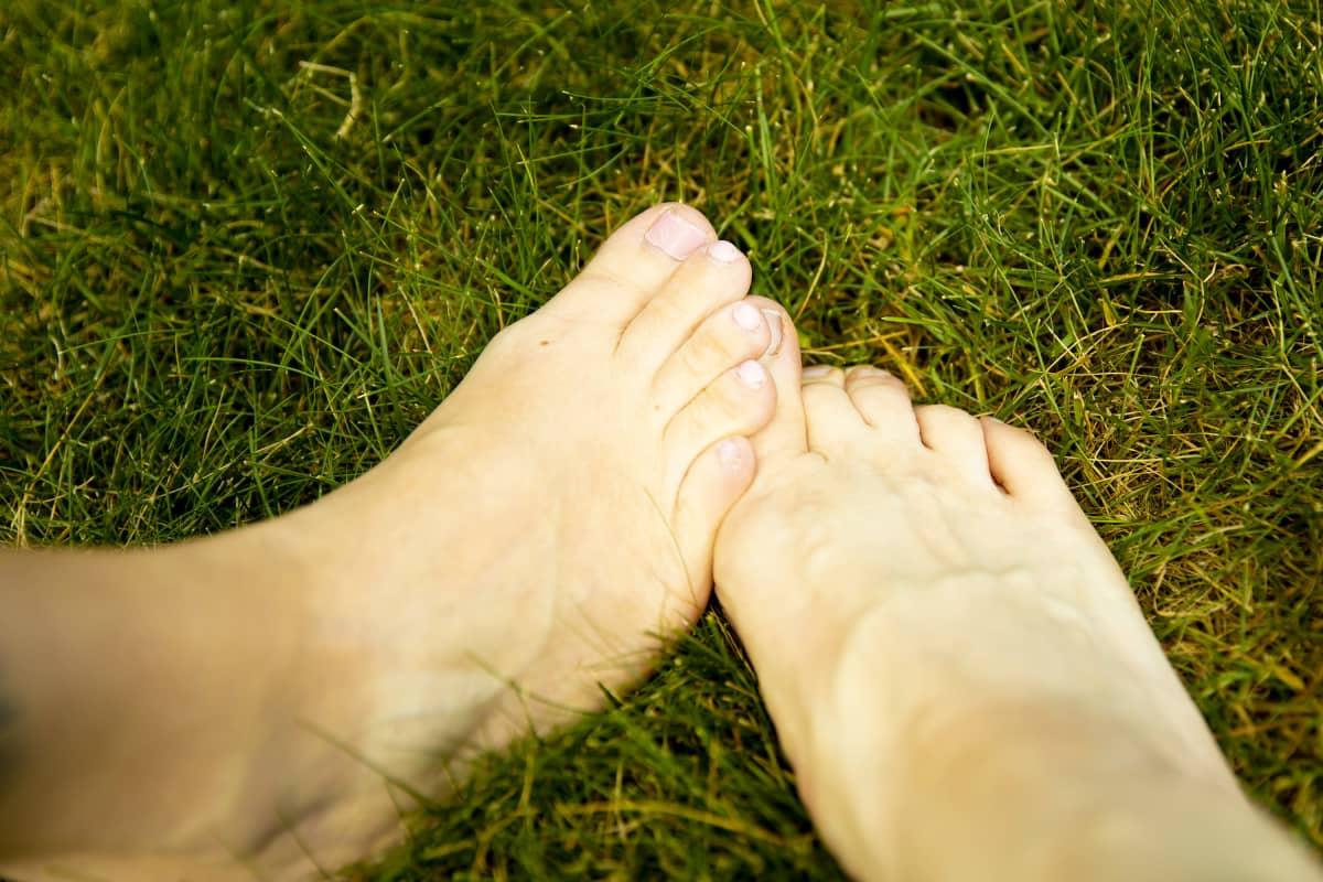 Kaksi jalkaa ristissä nurmikolla.