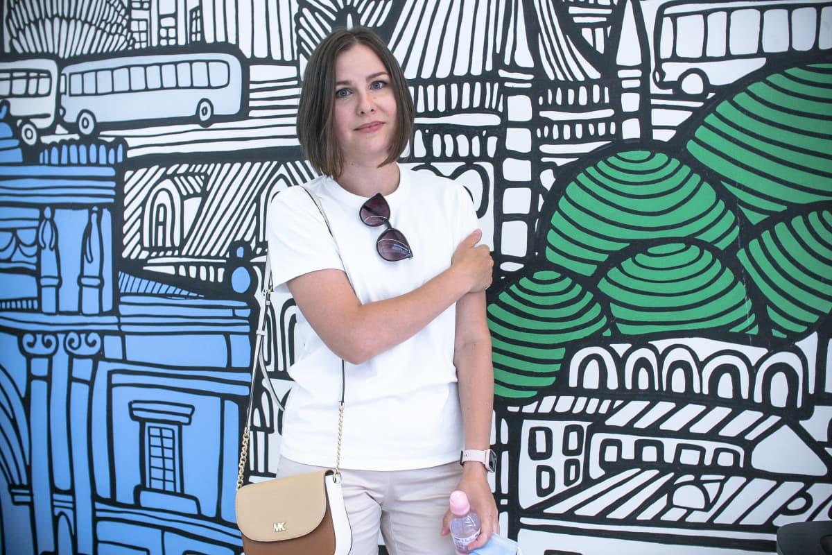 Nainen värikkäästi kuvioidun seinän edessä