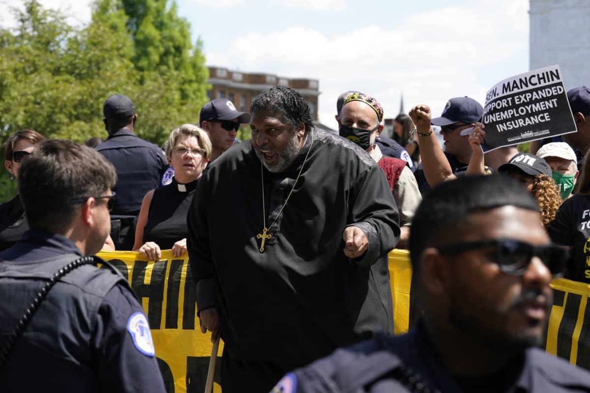 Hyvin lihava musta pastori risti kaulassa osallistuu mielenosoitukseen.