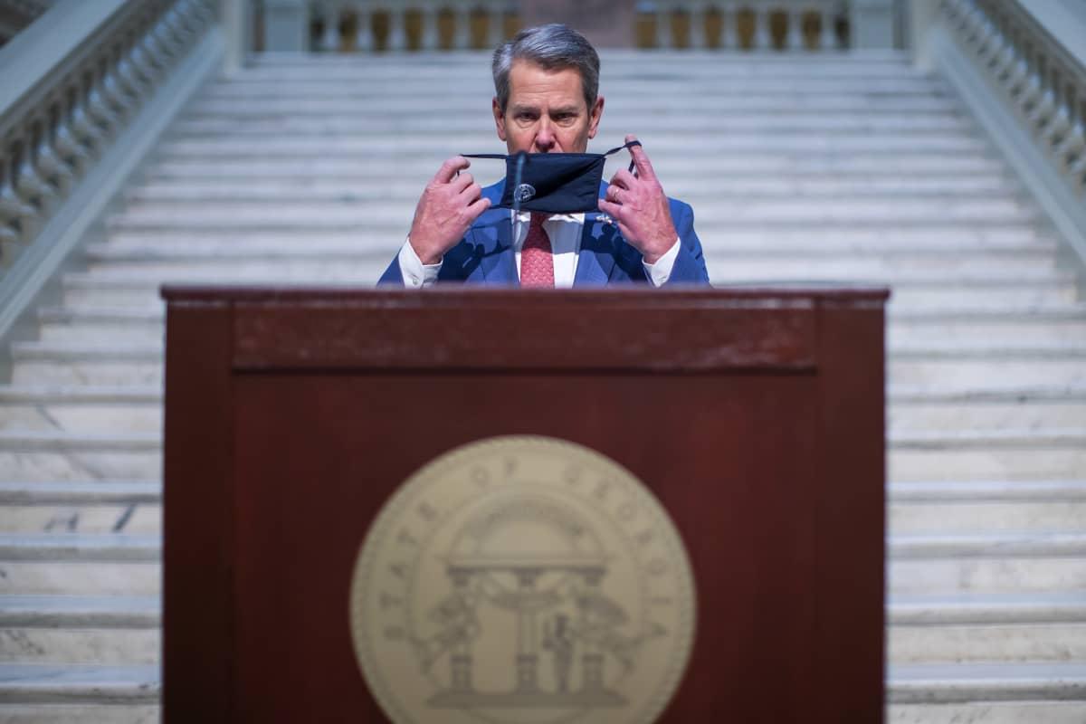 Georgian osavaltion kuvernööri Brian Kemp puhujapöntössä, ottaa juuri kasvomaskia pois tai laittaa sitä paikalleen.