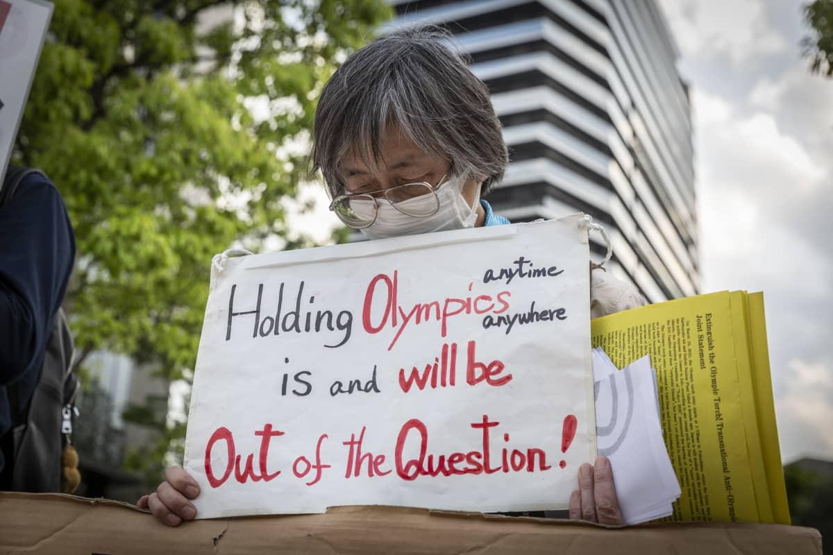 Nainen osoitti mieltään Tokion olympialaisia vastaan kesällä 2021.