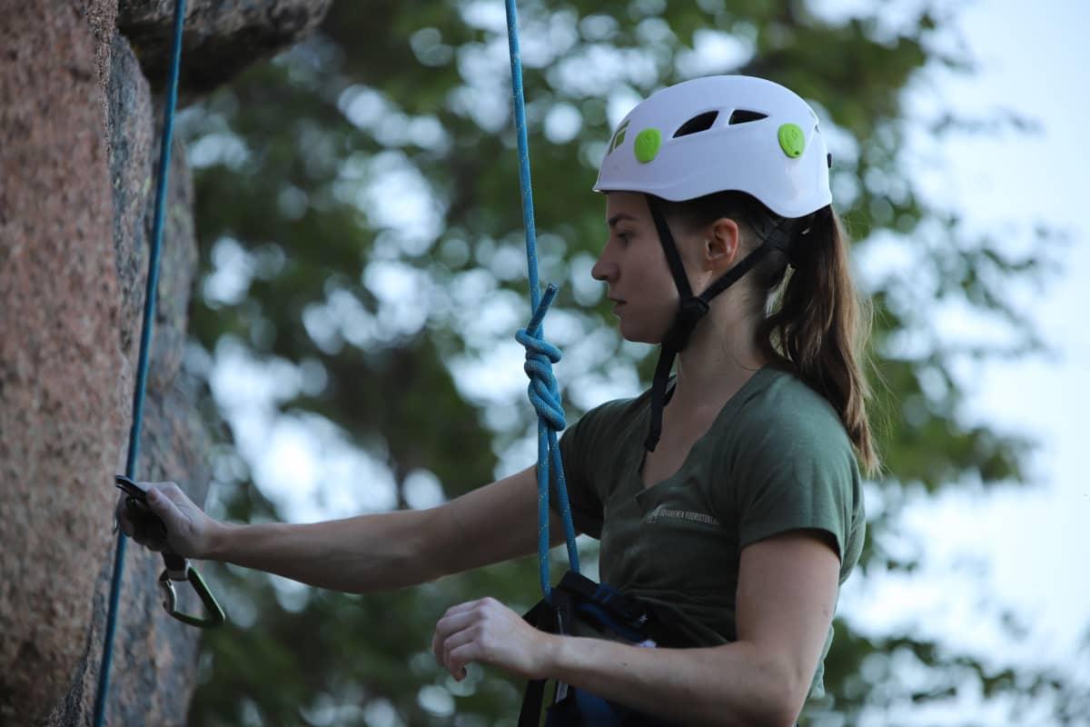 Kypäräpäinen Asta Heikkala roikkuu köydessä pystysuoran kallioseinämän edessä.