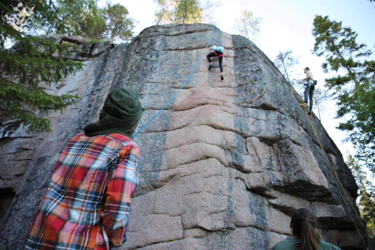Ruutupaitainen Antti Antikainen varmistaa köyden kanssa, kun turkoosipaitainen tytär Pinja kiipeää korkealla kallioseinämällä.