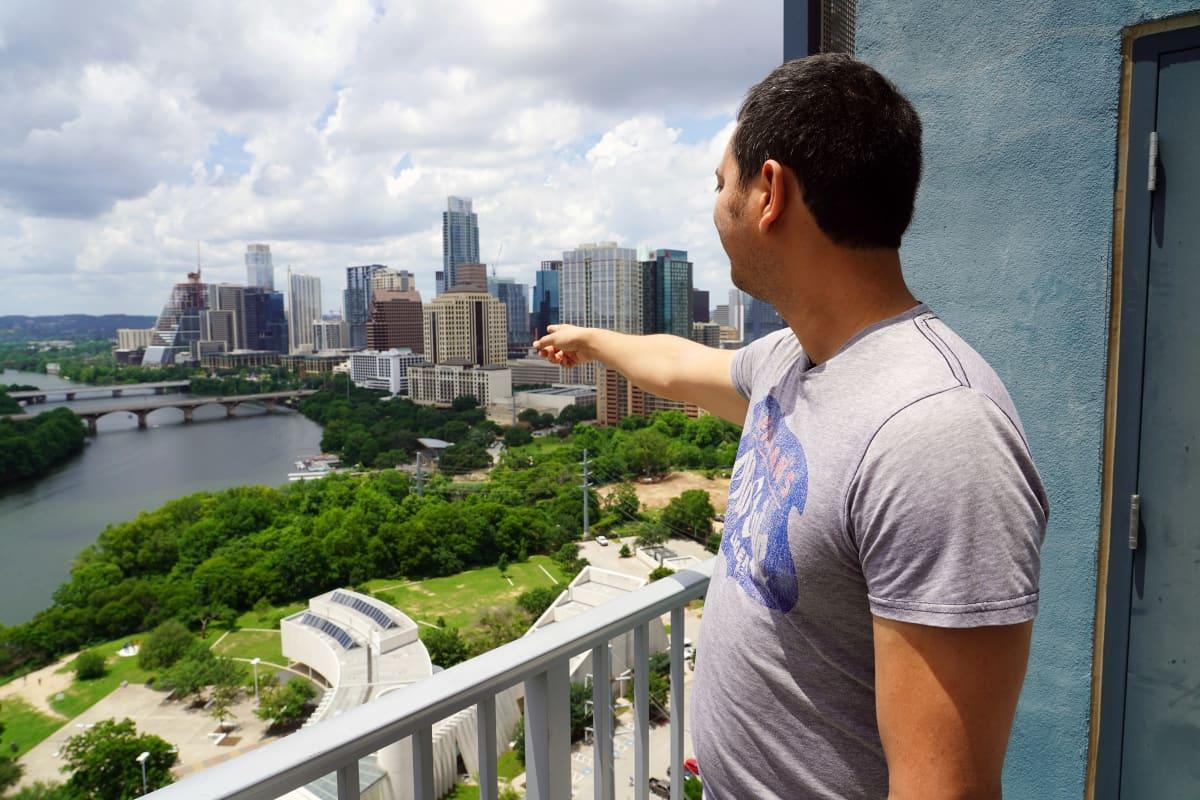 Mies osoittaa parvekkeelta näkyvää kaupungin keskustaa