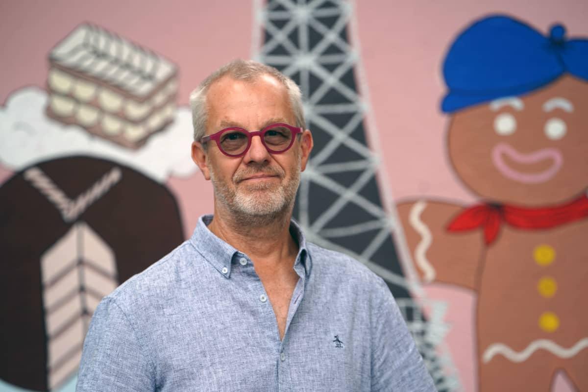 Mies poseeraa kameralle, taustalla värikäs teos, jossa kuvattuna piparkakku-ukko.