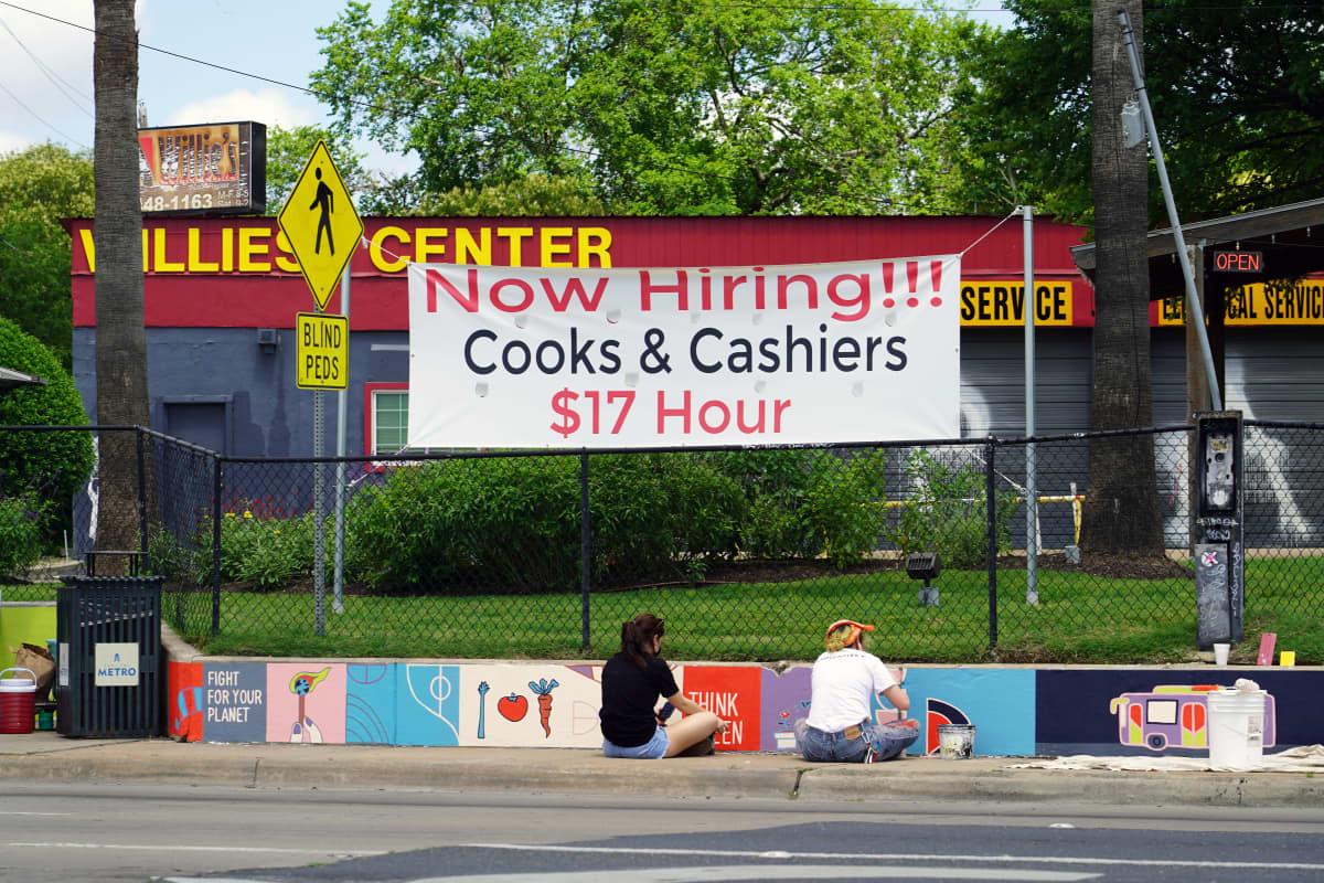 Vapaita ravintola-alan työpaikkoja mainostava kyltti kadunvarressa.