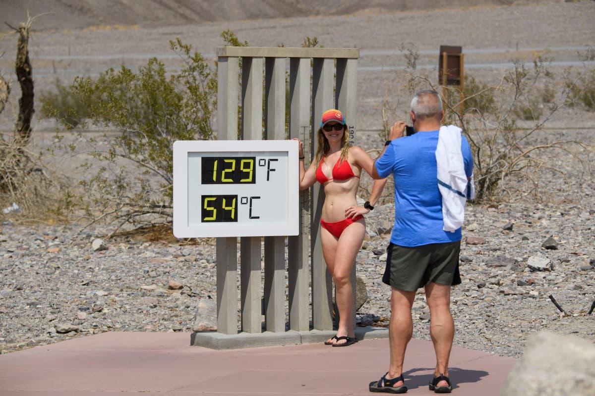 Mies ottaa bikiniin pukeutuneesta naisesta valokuvan lämpötilamittarin näyttäessä 54 astetta. .