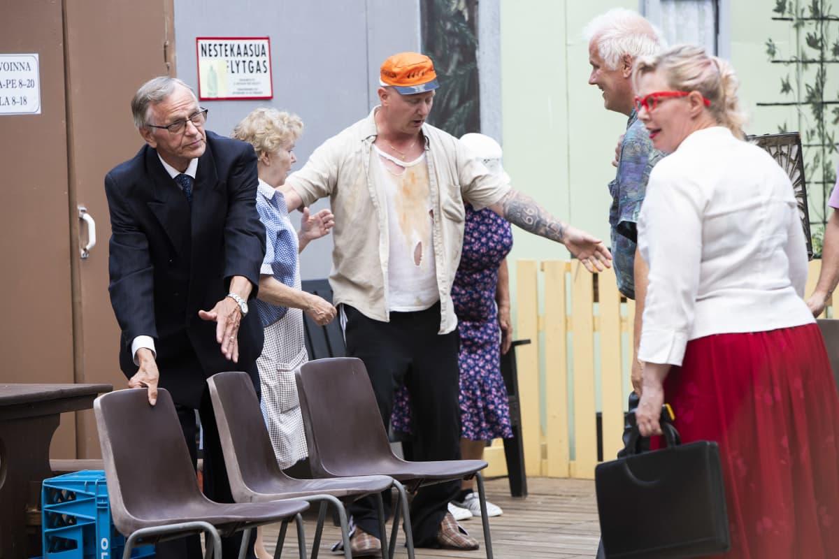 Kyläyhdistyksen puheenjohtaja Pekka Pönkä (Erkko Koskinen) ja Lavikainen (Janne Laukkanen) ohjaavat kyläläisiä istumaan.