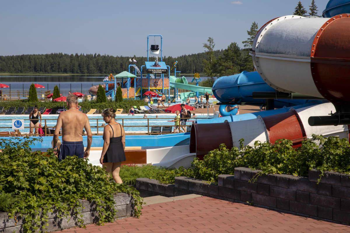 Kouvolan Tykkimäki Aquaparkissa pariskunta kävelee altaalle, taustalla altaita ja vesiliukumäkiä.