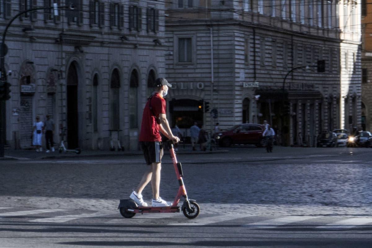 Henkilö sähköpotkulaudalla Rooman kadulla.