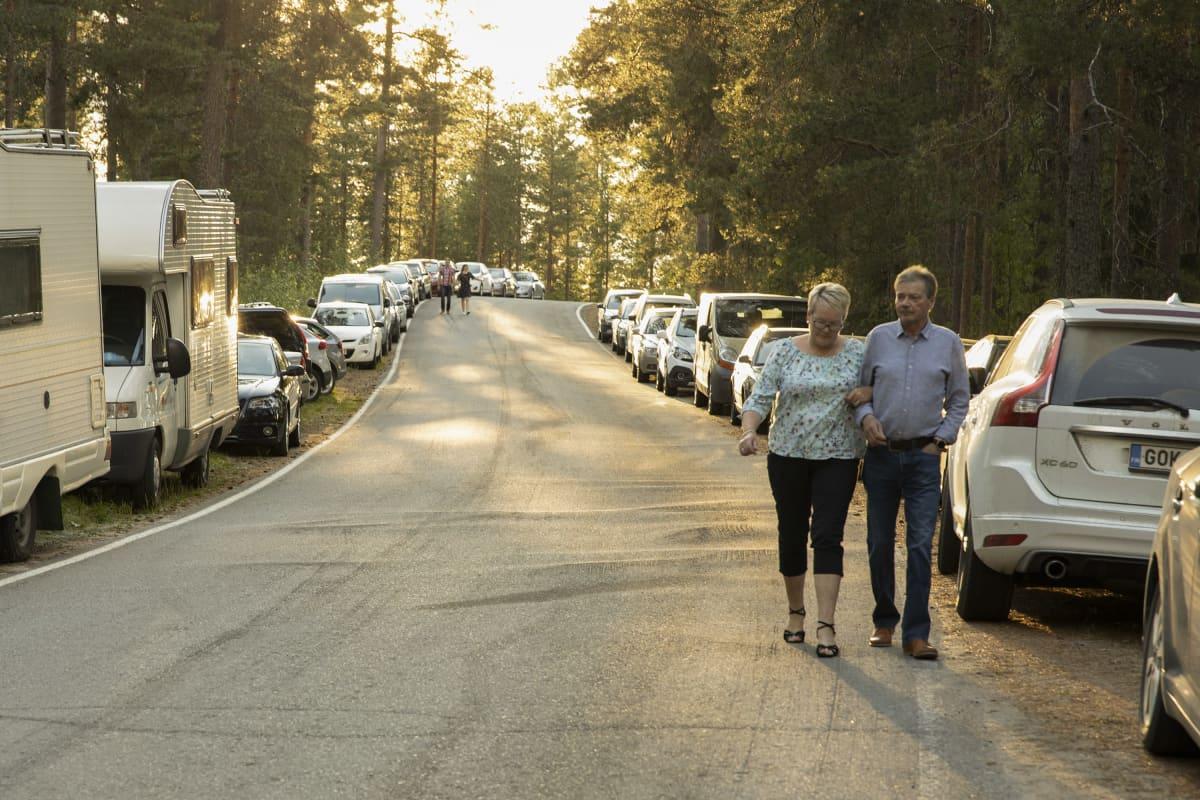 Pariskunnat kävelevät tiellä ilta-auringon valossa. Tien varret ovat täynnä pysäköityjä henkilö- ja matkailuautoja..