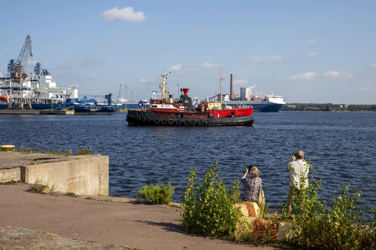 hinausalus Ajax kuljettaa majakkalaiva Kemiä kohti Kantasatamaa, Kemi kiinnitetty hinausaluksen kylkeen, ihmiset ottavat kuvia laiturilta