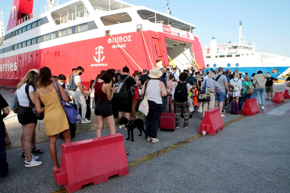 Matkustajat jonottavat lauttaan satamassa.