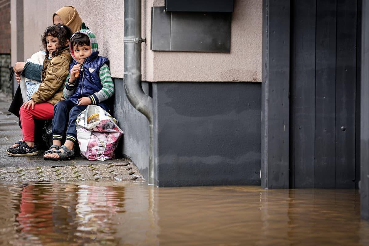 Asukkaat istuvat vesirajan vieressä kadulla.