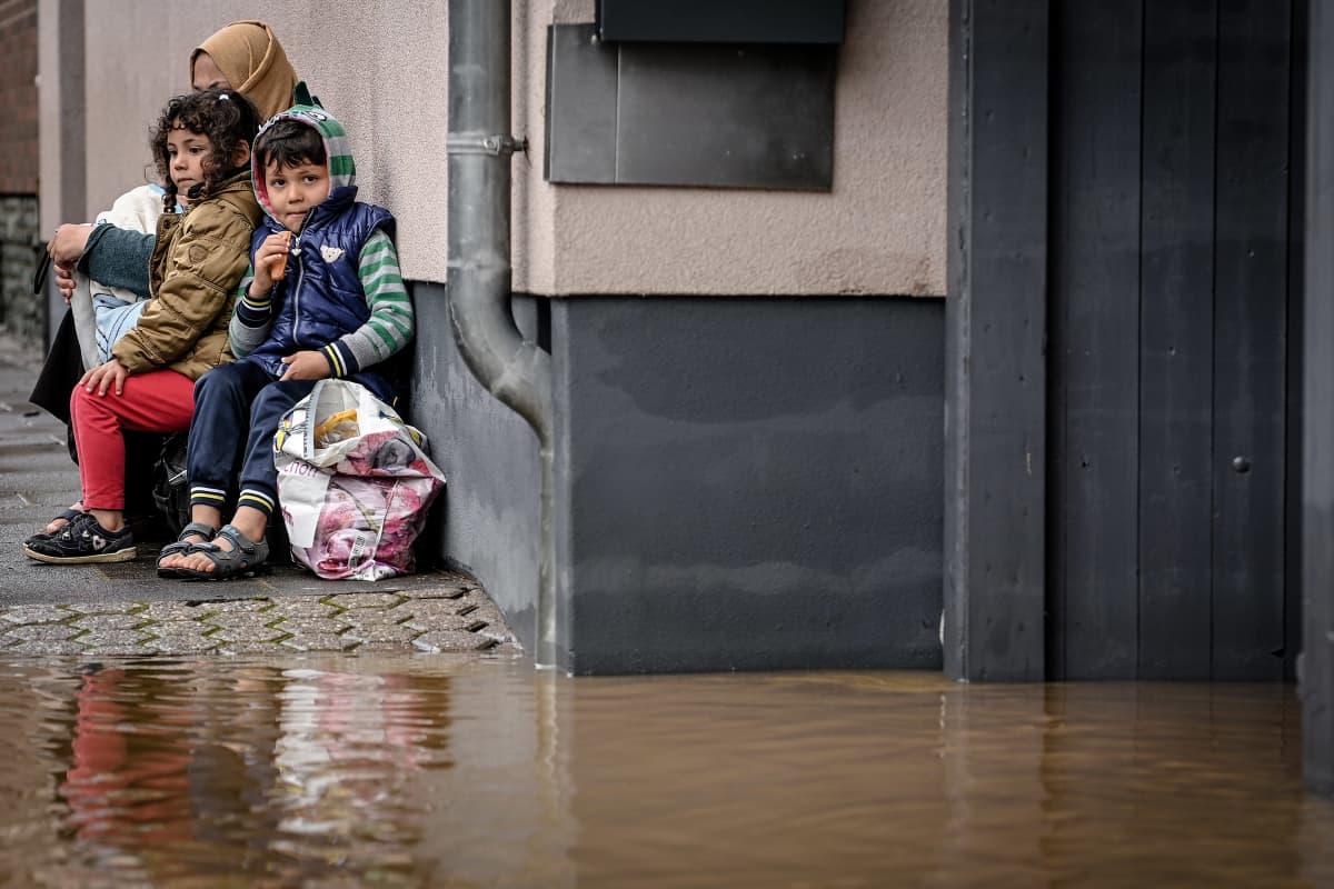 Perhe istuu talon edessä suojassa tulvavedeltä.