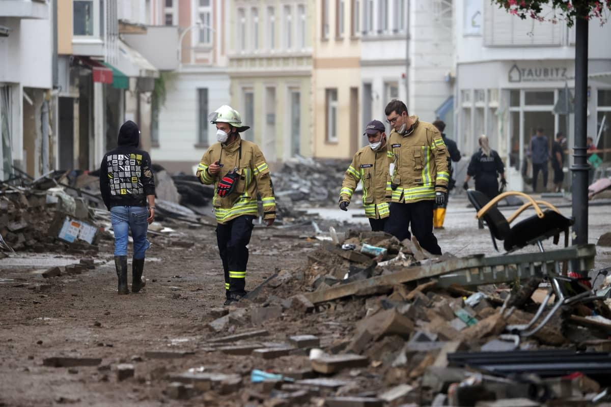 Pelastustyöntekijöitä kadulla olevan romun keskellä.