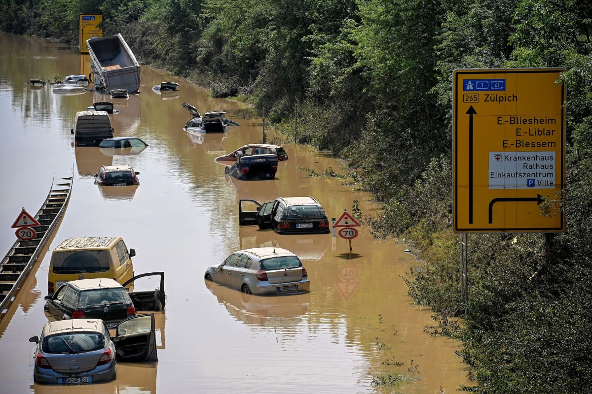 Autoja seisoo sikin sokin ruskean tulvaveden peittämällä. Vedessä kulkevat myös rautatieraiteet.