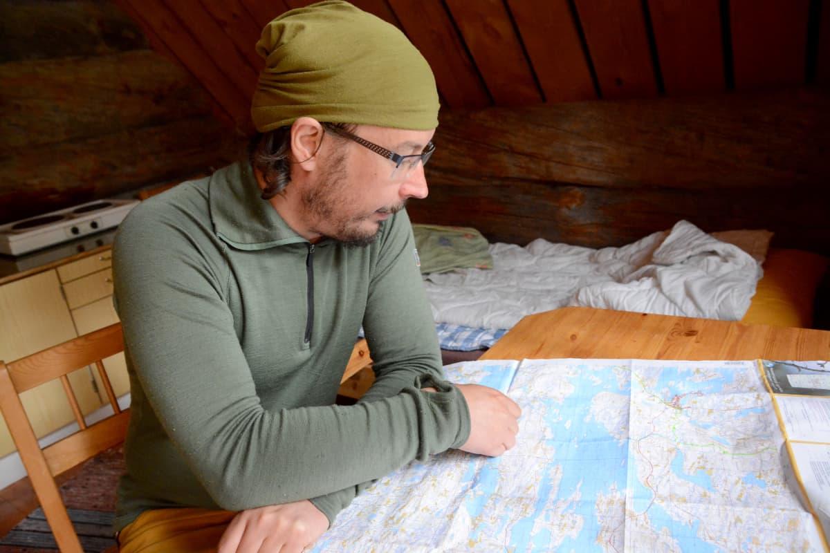 Kuvassa mies katsoo karttaa