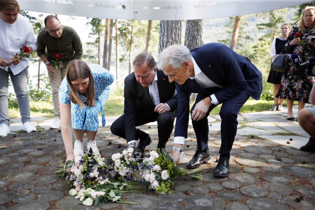 Kolme henkilöä asettelee kukkia maahan muistotilaisuudessa.