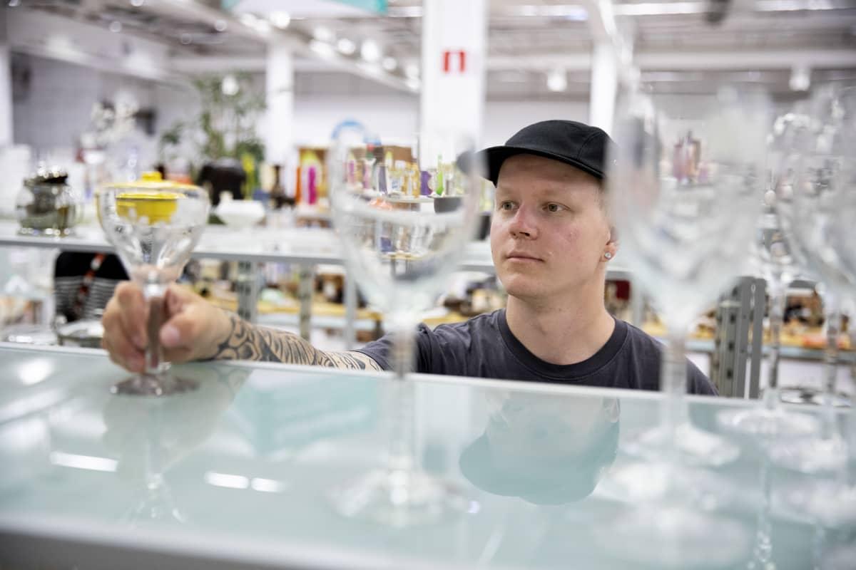 Mies kurkottaa hyllylle katsoakseen lasiesinettä kirpputorilla.