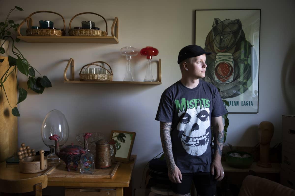 Iivari Viilosmaa kotonaan huoneessa, joka on täynnä design-keräilytyotteita.