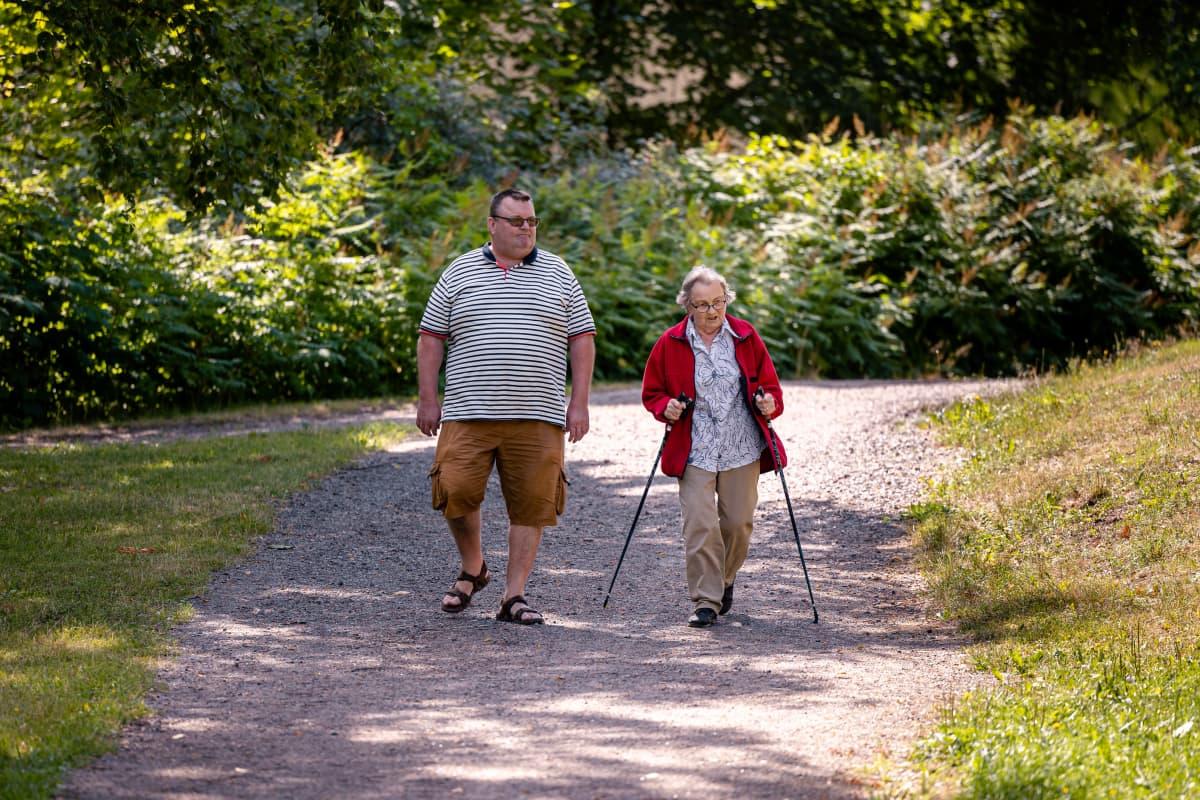Markku Kostiainen kävelyllä puistossa iäkkään äitinsä Raili Kostiaisen kanssa.