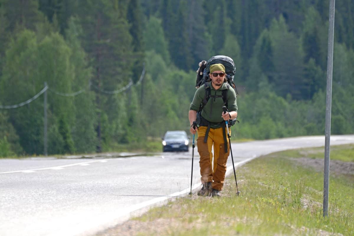 Mies kävelee valtatien reunaa pitkin rinkka selässään.