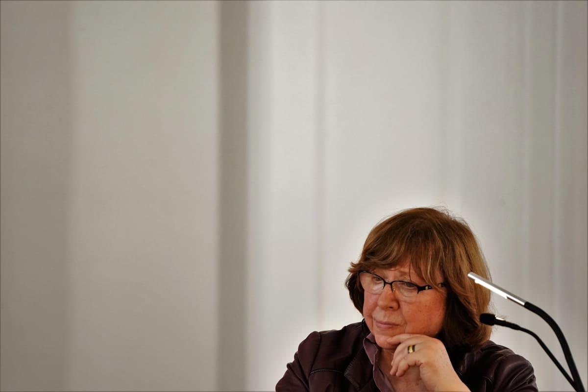 Silmälasipäinen Svetlana Aleksijevitš istuu kahden mikrofonin ääressä mietteliään näköisenä. Taustalla näkyy valkoista seinää.