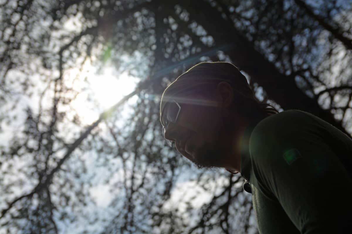 Aurinko paistaa ja mies katsoo kaukaisuuteen.