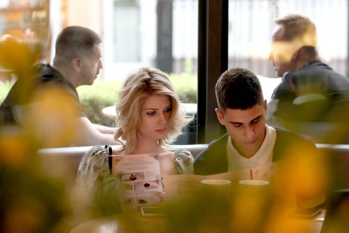 Mies ja nainen istuvat kahvilassa.