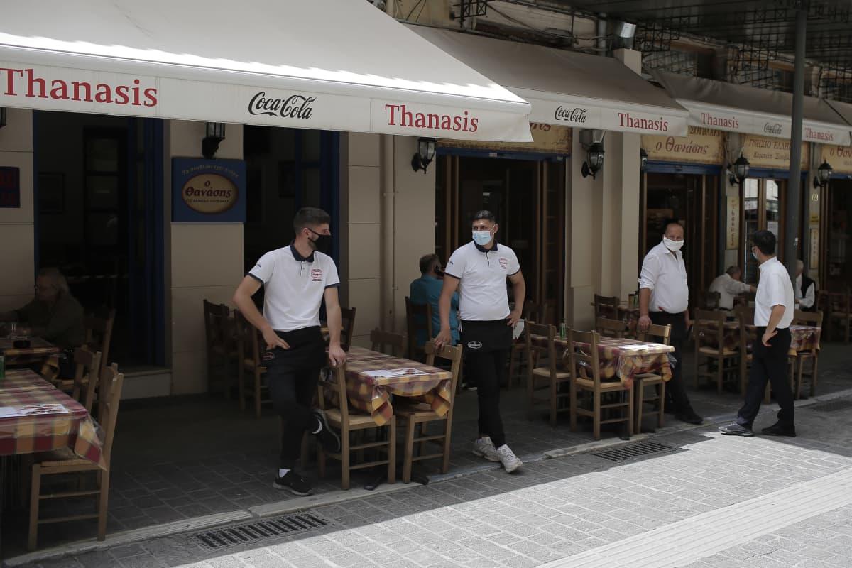 Tarjoilijat seisovat ravintolan terassilla.