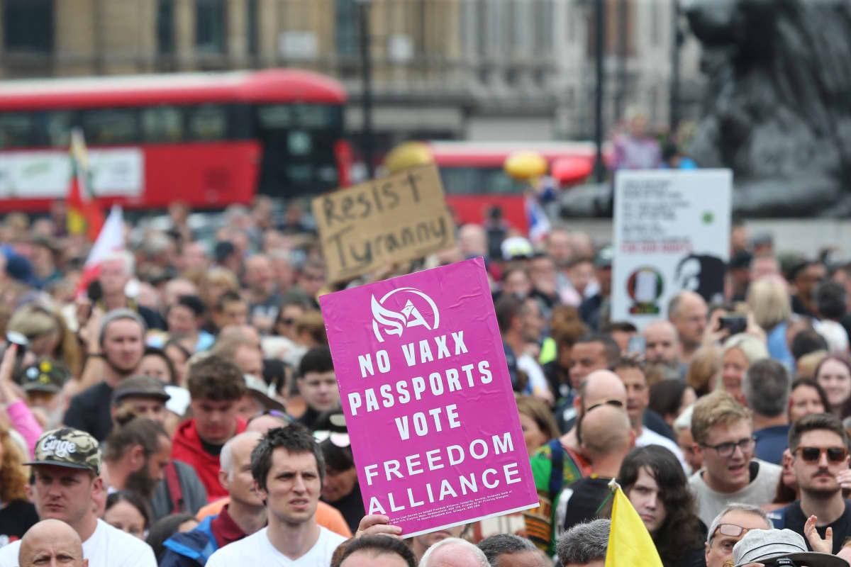 Mielenosoittajia. Kyltissä vastustetaan rokotepassia.