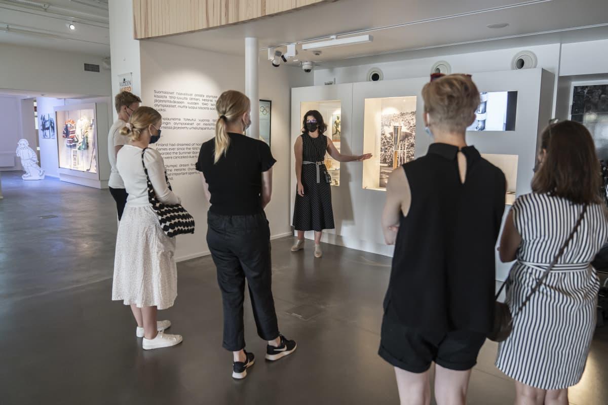 Museolehtori Jonna Kokkola esittelee Helsingin Olympialaisten Olympiasoihtua Urheilumuseon opastetulla yleisökierroksella.