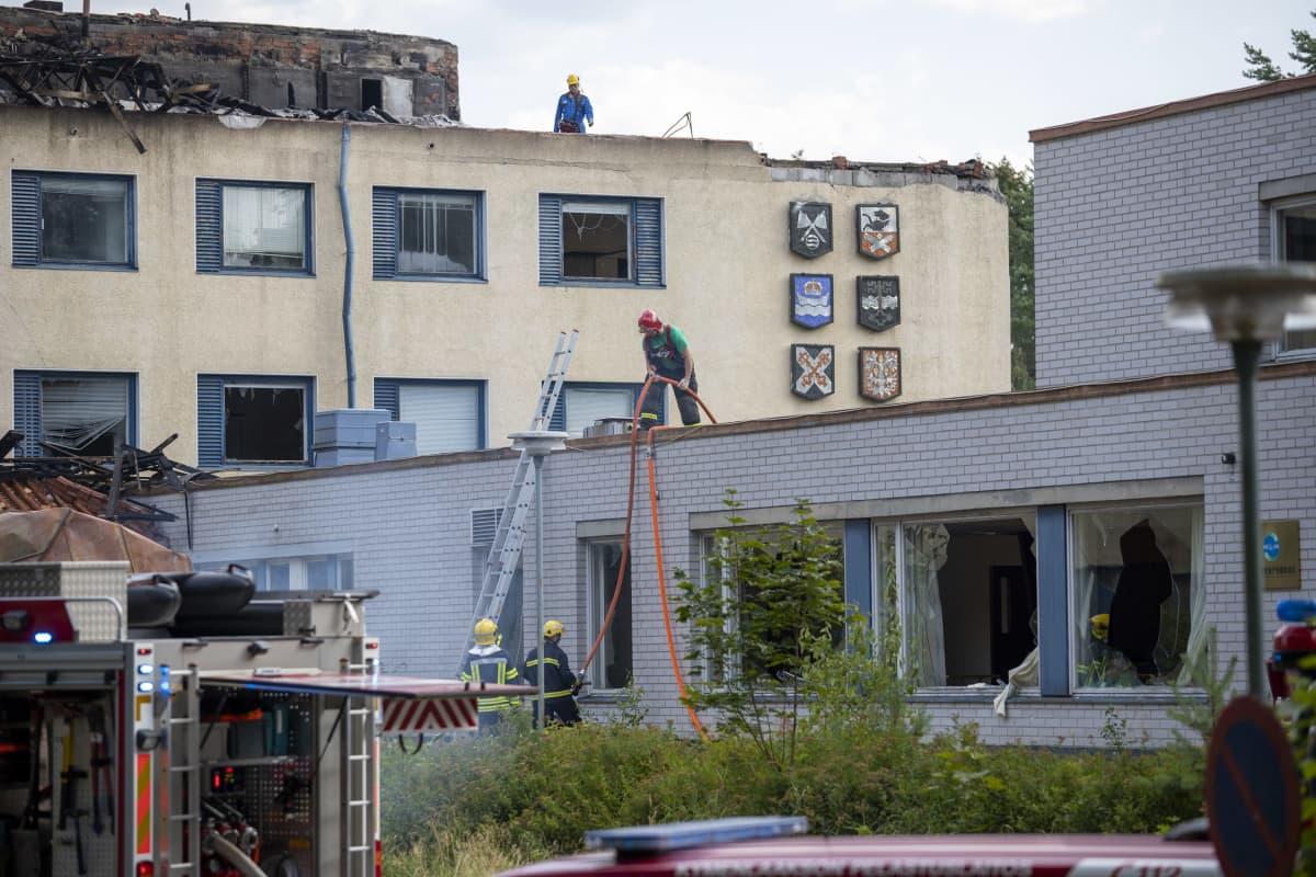palomiehiä jälkisammutustöissä katolla